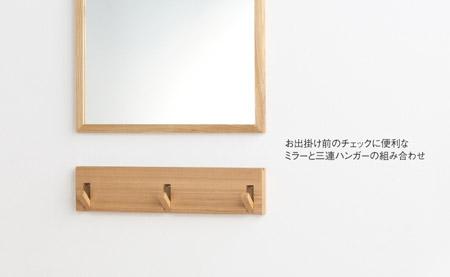 壁に付けられる家具の3連ハンガーと鏡の組み合わせ